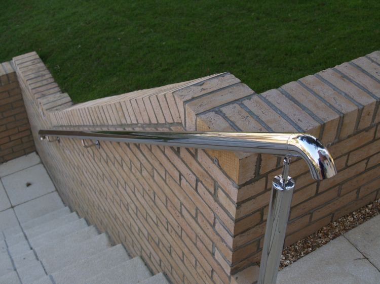 A stainless steel railing lines outside steps